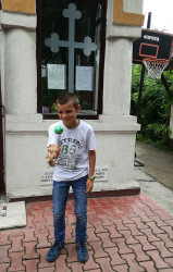 Florina  Marian, one of the priest&#039s sons, playing kendama after the Divine Liturgy at the Nefliu Parish.  2017-07-16 16:33:49